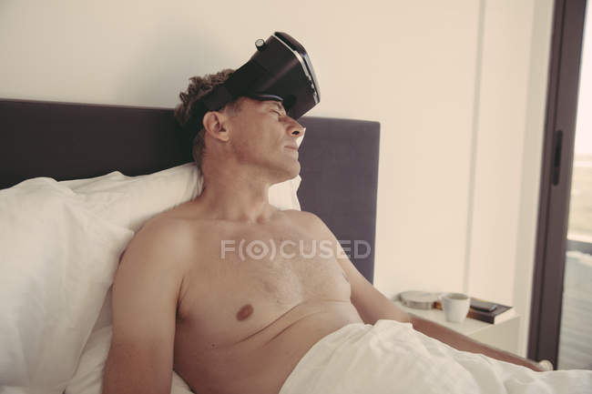 Tired man wearing VR glasses in bed — Stock Photo