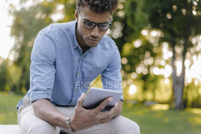Hombre afroamericano joven mirando el teléfono celular en el parque - foto de stock