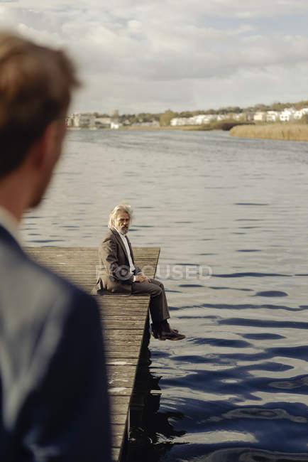 Anziano seduto sul molo al lago con l'uomo in primo piano — Foto stock