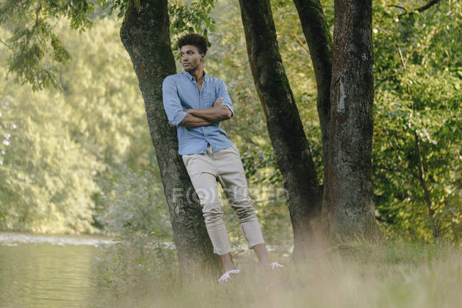 Young african american man leaning on tree in park — Foto stock