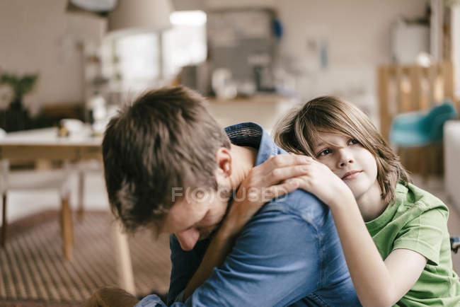 Sohn tröstet traurigen Vater zu Hause — Stockfoto