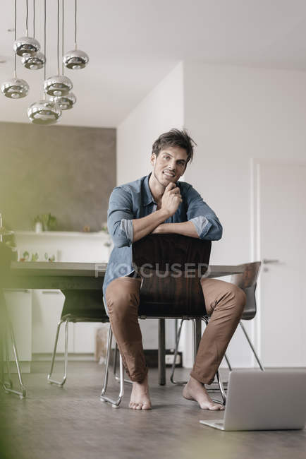 Portrait of smiling young man sitting on chair in a loft — Stock Photo