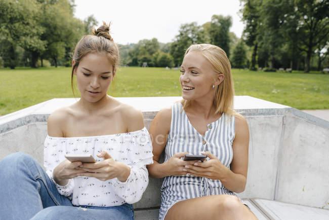 Duas jovens felizes com telefones celulares no parque de skate — Fotografia de Stock