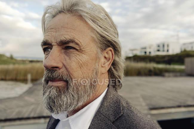 Portrait of serious senior man at lakeshore — Stock Photo