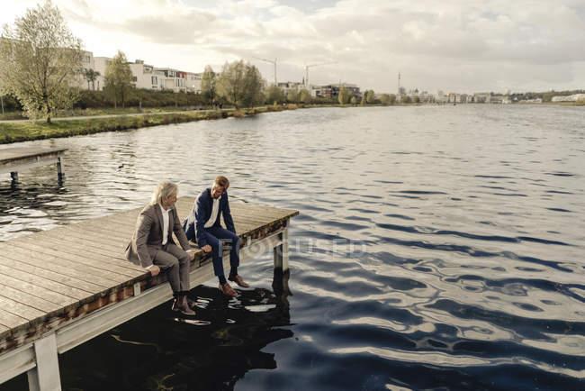 Due uomini d'affari seduti sul molo al lago e parlare — Foto stock