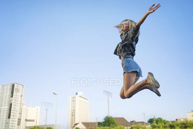 Happy young woman jumping in air — Stock Photo
