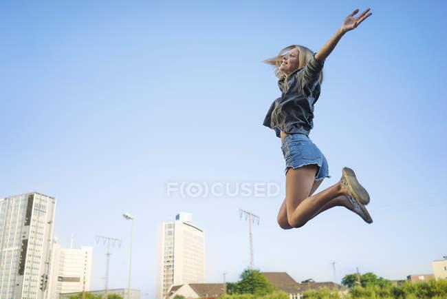 Donna giovane felice saltando in aria — Foto stock