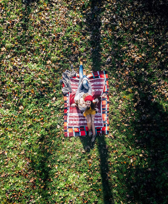 Two happy women sitting on blanket in an autumnal meadow — Stock Photo