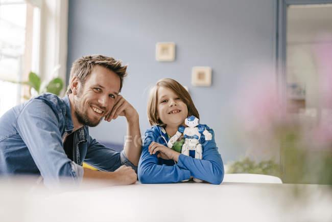 Портрет счастливого отца и сына с роботом дома — стоковое фото