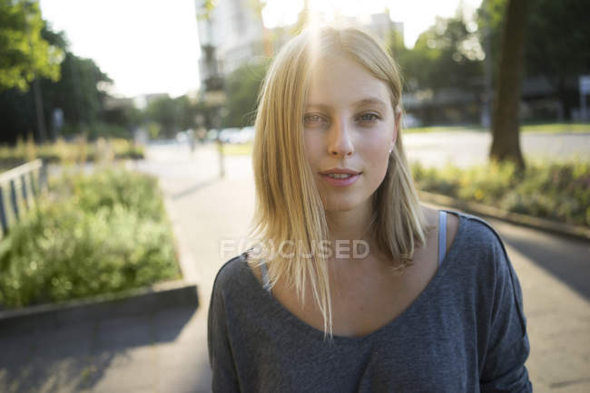 Portrait of blonde young woman with back light — Stock Photo