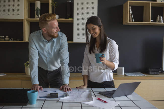 Smiling man and woman with plans on table at home — Stock Photo