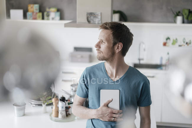 Man with tablet standing in the kitchen and looking at distance — Fotografia de Stock