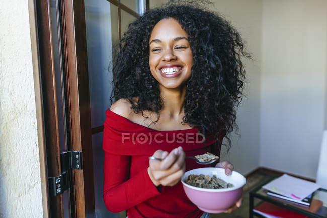 Retrato de una joven riendo comiendo cereales - foto de stock