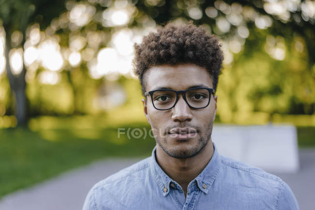 Portrait of young african american man wearing glasses in park — Stock Photo