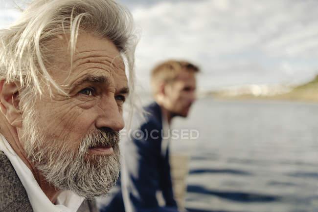 Ritratto di un uomo anziano serio al lago con l'uomo sullo sfondo — Foto stock