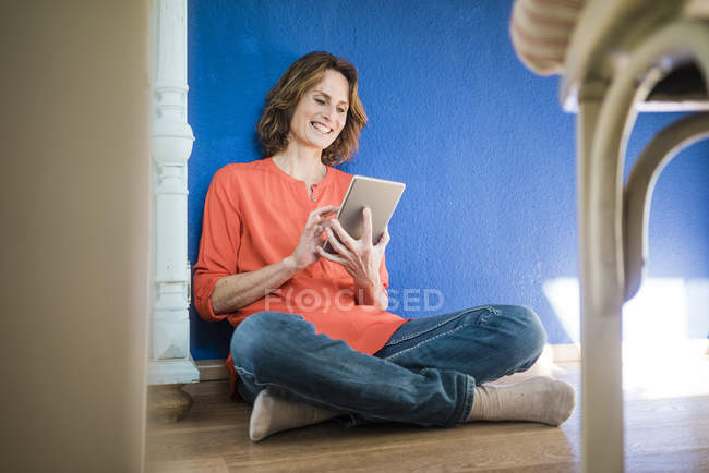 Smiling woman sitting on the floor at home and using tablet — Stock Photo