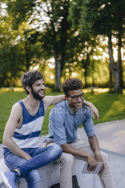Two happy multicultural friends sitting in skatepark — Stock Photo