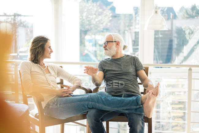 Relaxed mature couple talking on chairs at home — Stock Photo