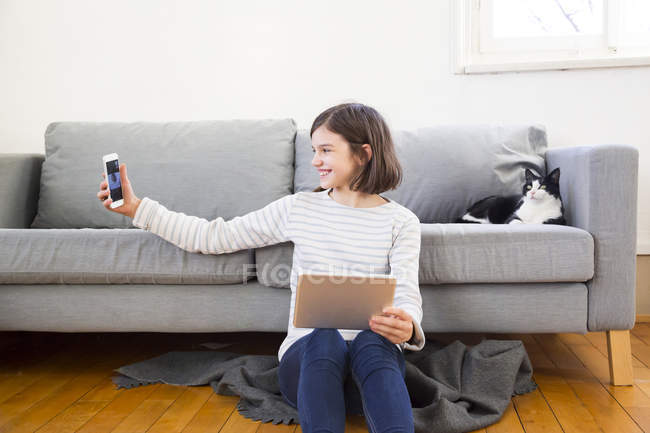 Happy girl with tablet sitting on the floor of the living room taking selfie with smartphone — Stock Photo