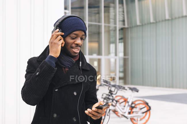Italia, Milán, hombre afroamericano con smartphone y auriculares - foto de stock