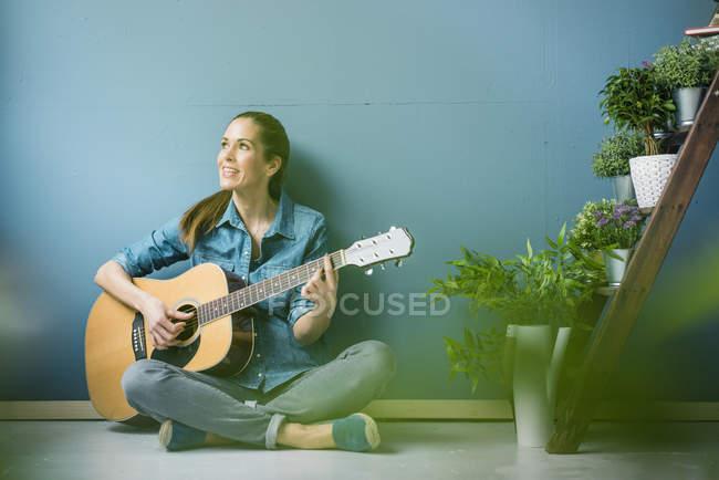 Donna rilassante nella sua casa con piante in vaso, suonare la chitarra — Foto stock