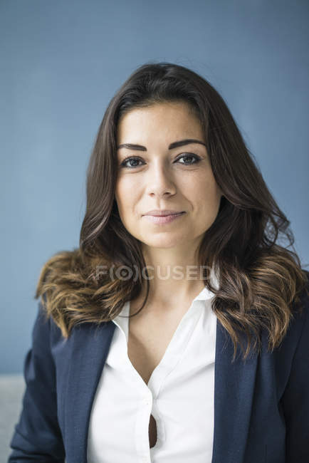 Portrait of smiling businesswoman looking at camera on blue background — Stock Photo
