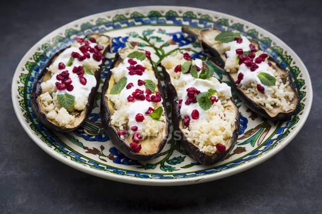Gefüllte Auberginen, Couscous, Joghurtsauce, Minze und Granatapfelkerne — Stockfoto