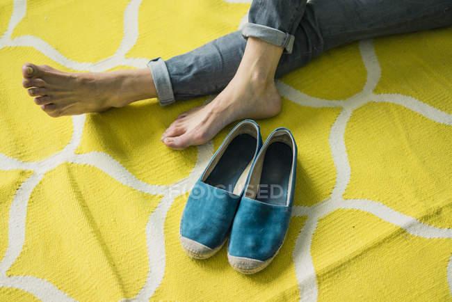 Обрізаний образ жінки розслабляє на жовтому килимі — стокове фото