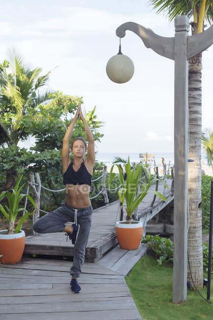 Indonesia, Bali, woman practicing yoga, tree position — Stock Photo