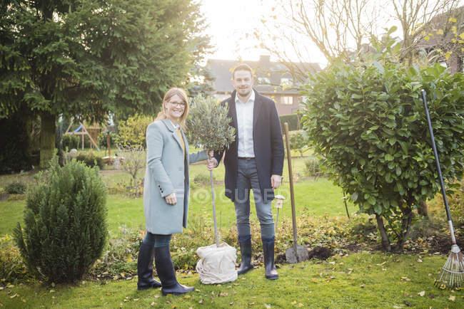 Портрет усміхнених пар стоячи в саду восени посадка дерево — стокове фото