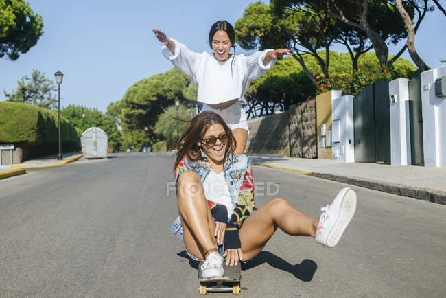 Two laughing friends together on skateboard — Stock Photo