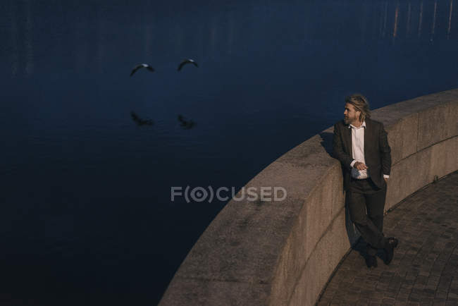 Anziano in piedi al lago in serata — Foto stock