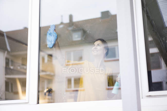Smiling woman at home cleaning window — Stockfoto