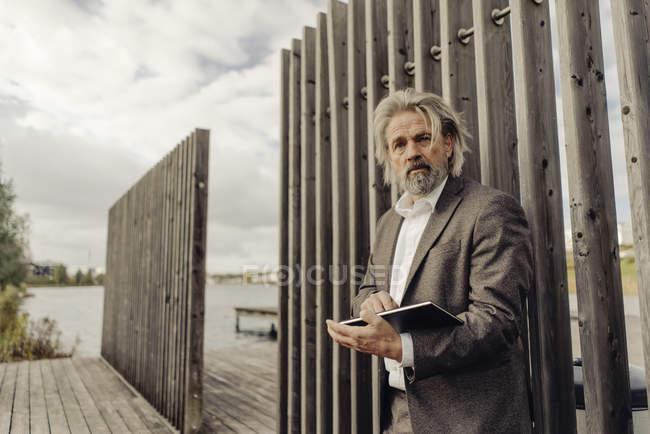Anziano con tablet a Lakeside — Foto stock