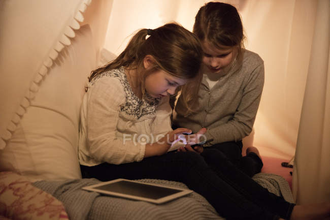 Two girls with cell phone and tablet in children's room — Stock Photo