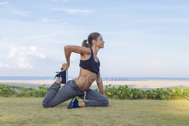 Indonesia, Bali, woman stretching legs — Stock Photo