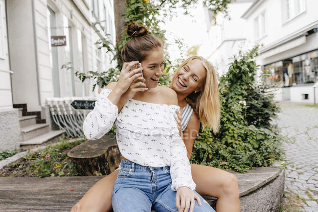 Two happy young women with cell phone in city — Stock Photo