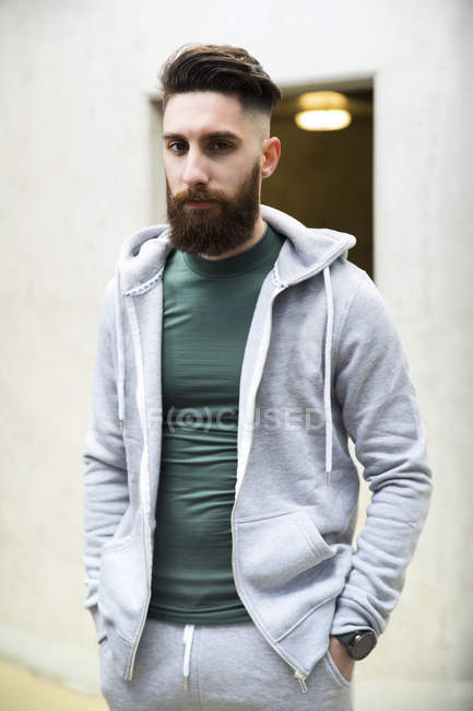 Portrait of a young man wearing a track suit, hands in pockets — Stock Photo