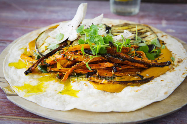 Pulled Chicken Wrap, carrot, grilled aubergine, curry hummus, herbs on chopping board — Stock Photo