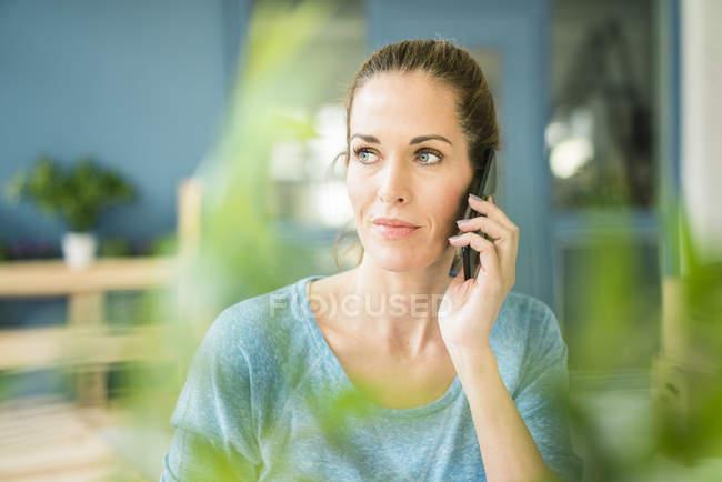 Mulher falando ao telefone em sua nova casa — Fotografia de Stock