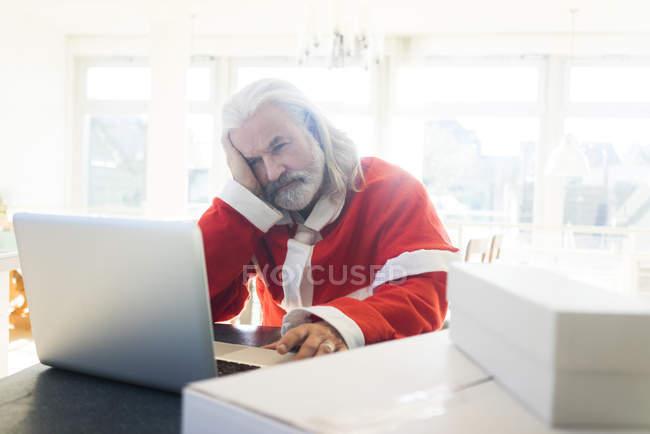 Розчарований Санта використання ноутбука вдома — стокове фото
