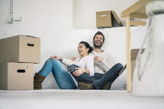Laughing couple sitting in new home surrounded by cardboard boxes — Stock Photo