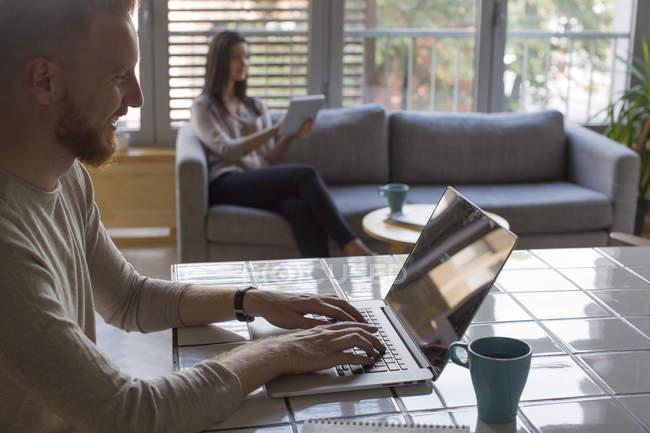 Homem com laptop e mulher com tablet em casa — Fotografia de Stock
