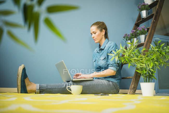Bella donna nella sua casa, decorata con piante, utilizzando laptop — Foto stock