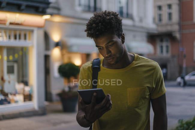 Мужчина африканский американец смотрит на скрижаль в городе в сумерках — стоковое фото