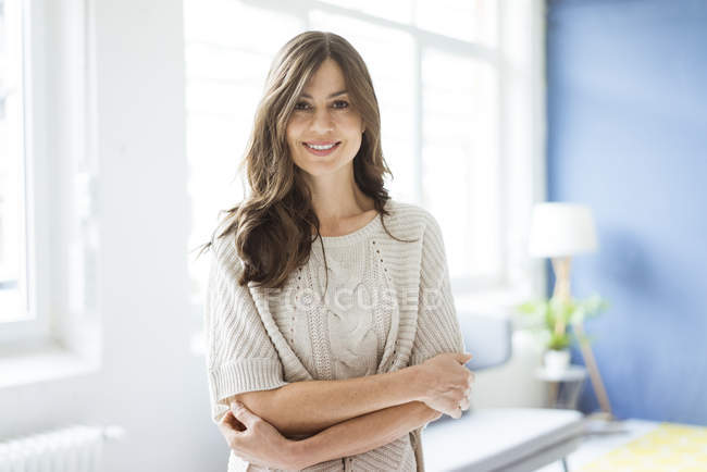 Portrait de femme souriante debout dans une pièce lumineuse avec fenêtre — Photo de stock
