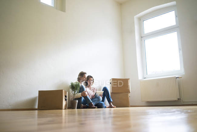 Mature couple sitting on floor in empty room next to cardboard boxes and using tablet — Stock Photo