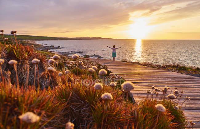 Italy, Sardinia, Lu Litarroni, senior woman on wooden boardwalk at sunset — Stock Photo