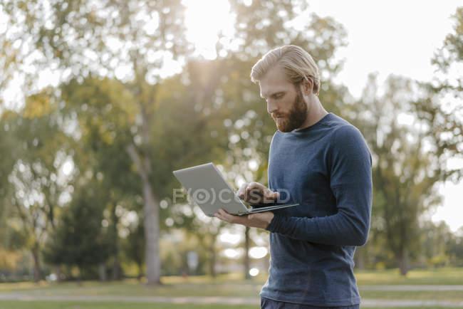 Uomo che utilizza il computer portatile in un parco — Foto stock