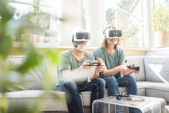 Mature couple sitting on couch at home, wearing VR glasses and playing video game — Stock Photo